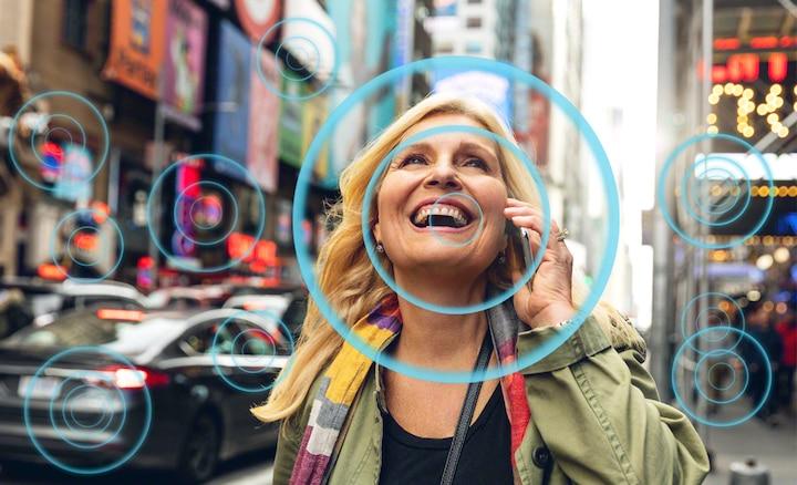 Slika ženske na polni ulici, ki prikazuje, kako Voice Zoom2 olajša poslušanje govora